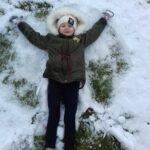 Zima - dziecko leżące na śniegi
