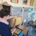 Nauczyciel prezentuje akcesoria pszczelarskie